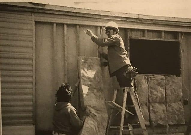 Installing-insulation-batt-into-a-mobile-home-with-siding-removed-1