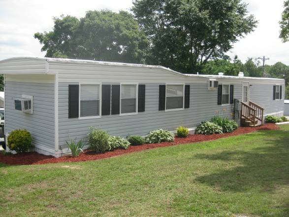 Plainting small shrubs around the perimeter of a mobile home with mulch