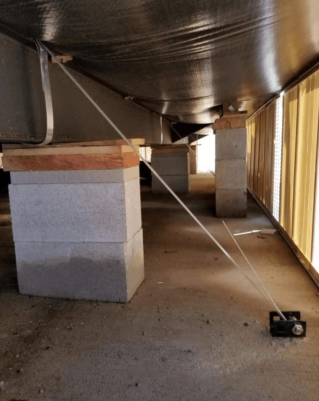 Underbelly And Blocks Under A New Manufactured Home With Tie Downs
