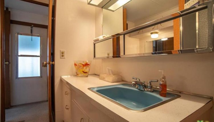 1962 Skyline is a Vintage Mobile Home Beauty - master bathroom with teal sink