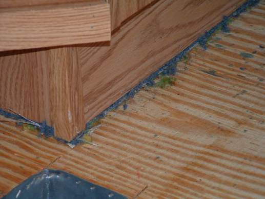 Carpet under a manufactured homes cabinets due to building process -- vinyl tile in manufactured-homes