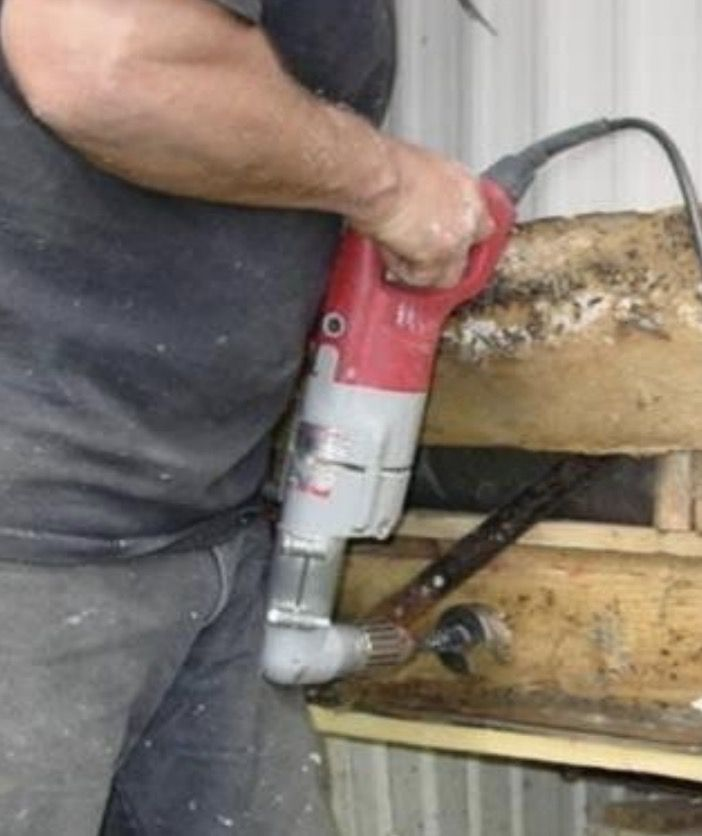 drilling a hole into a mobile rim joist home rim joist to blow insulation into it
