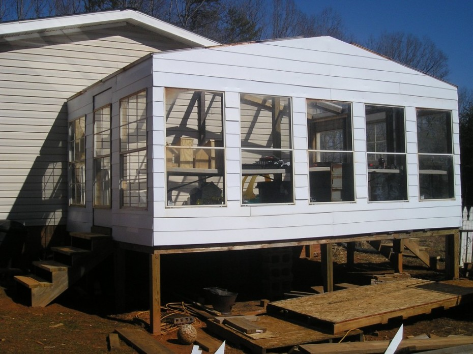 greenhouse built onto a manufactured home for homesteading