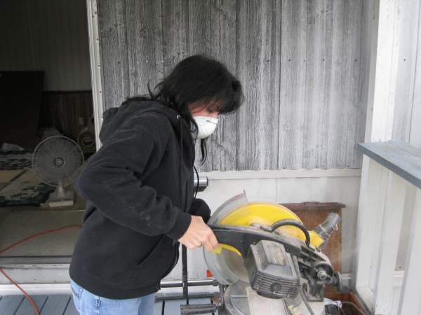 Diy manufactured home remodel - homeowner using a saw