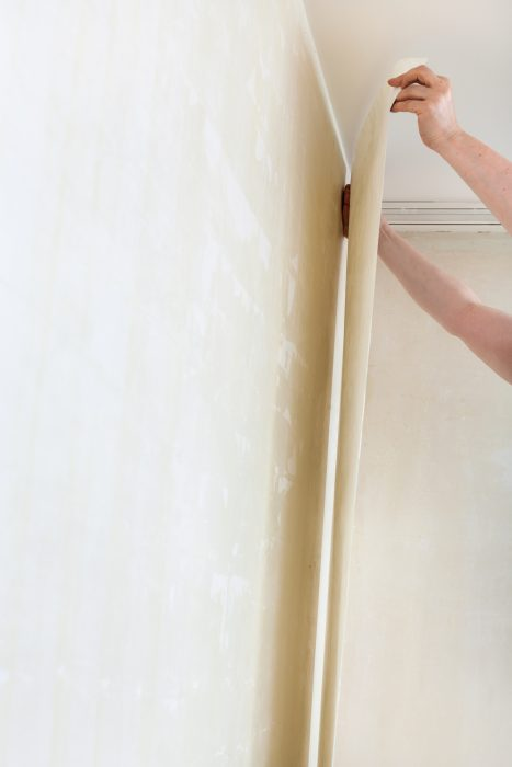 questions about painting vinyl mobile home walls - worker hangs wallpaper on wall -